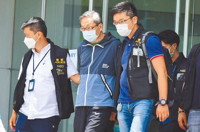 香港《蘋果日報》前主筆、英文版執行總編馮偉光,27日晚在香港機場欲搭機前往英國時遭港警拘捕。圖為壹傳媒行政總裁張劍虹17日被警方押離報社大廈。(中新社)