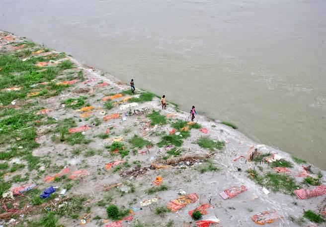 雨季到來,過去3周已經有多達150具新冠死者的遺體被洪水沖出來,漂浮在恆河岸邊。(圖/路透社)