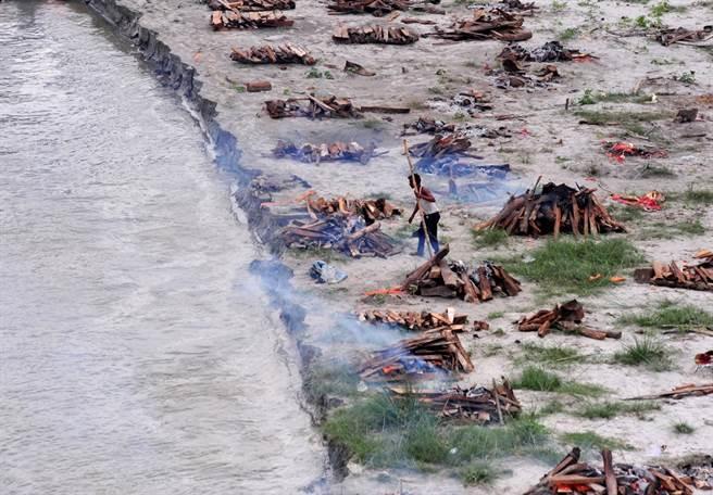 官員在恆河岸邊堆放一排又一排的火葬堆,準備將打撈起來的遺體就地火化。(圖/路透社)