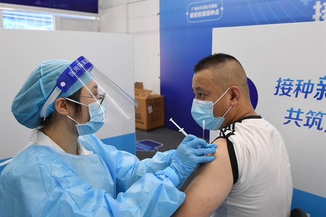 從廣州疫情來看,陸製疫苗能降低有症狀感染與重症風險。圖為廣州民眾施打疫苗。(圖/中新社)