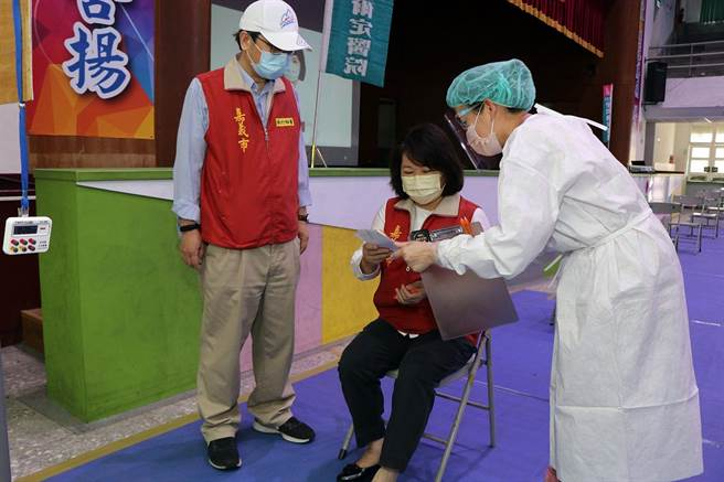 嘉義市長黃敏惠(中)視察設於北興國中的疫苗接種站,演示接種前聽取醫護人員的說明。(廖素慧攝)