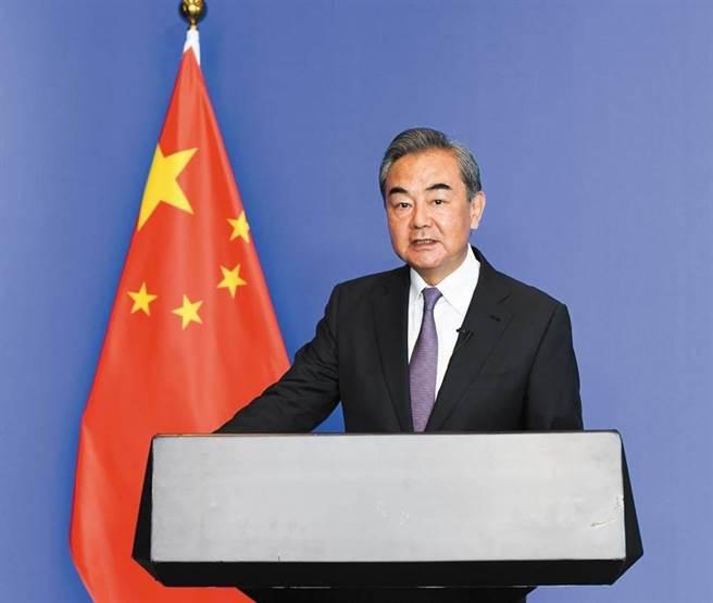 王毅步出世界和平論壇會場時,記者追著提問中美問題,王毅表示當然希望恢復對話。(新華社)