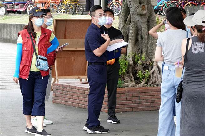 員警及新北市府人員4日赴八里左岸風景區,遇民眾違反規定拿下口罩飲食者,直接開罰。(黃世麒攝)