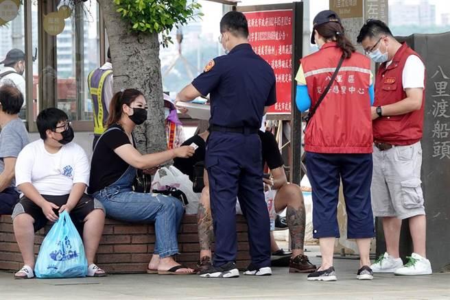民眾違反防疫規定,員警及新北市府人員直接上前開罰。(黃世麒攝)