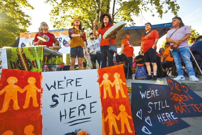 加拿大溫哥華民眾2日參加集會活動,悼念原住民寄宿學校的死者,前方海報寫著:「我們還在這裡」。日前加拿大原住民寄宿學校遺址發現大批遺骸,至今陸續發現共計上千具兒童遺骸。(新華社)