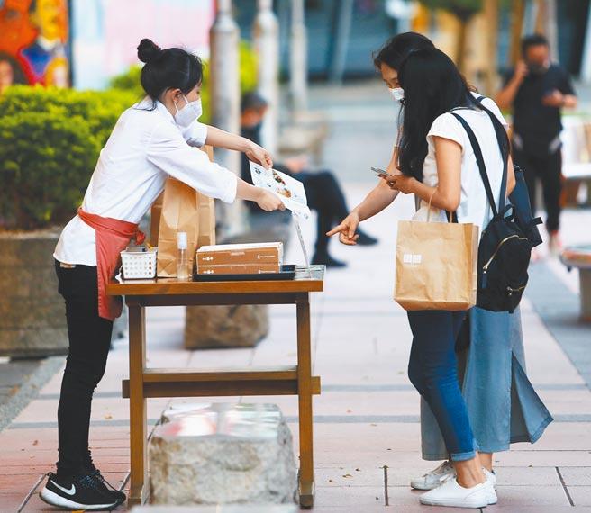 圖為信義商圈的美食商店,店員直接將攤位擺在人行道上以招攬顧客。(季志翔攝)
