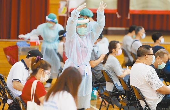 為期7天的台北市市場攤商疫苗接種專案6日持續進行,現場護理師大動作招呼剛抵達的民眾入座。(季志翔攝)