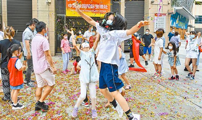 圖為大陸廣州市,小區居民慶祝解除封閉、封控管理。(中新社)