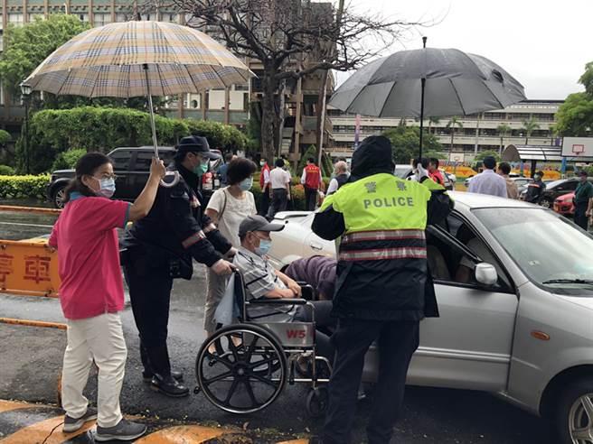 高雄連日大雨,維護秩序的員警們以及工作人員護送長者上車,就像照護自己的家人一樣。(圖片提供/高市府衛生局)