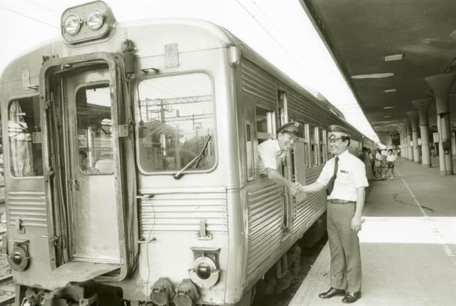 1979年,鐵路局光華號最後一班次列車自台北火車站開出,展現「白鐵仔」風采,站務人員與列車長握手致意。(黃紹川攝)