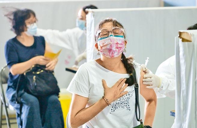 台北市首波校園教職員工疫苗開打,14日在網球中心接種站有教職員注射時,手輕撫胸口深呼吸放鬆全身。(王英豪攝)