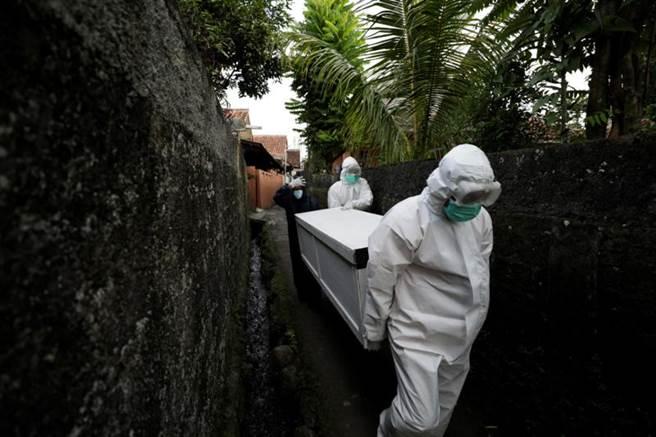 印尼單日死亡人數991人,穿著防護設備的志工忙著抬送棺木至墳場。(圖/路透社)