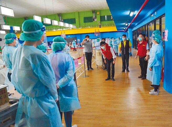 高雄巿長陳其邁(中)15日視察接種站,並向醫護人員鞠躬。(高巿府提供/曹明正高雄傳真)