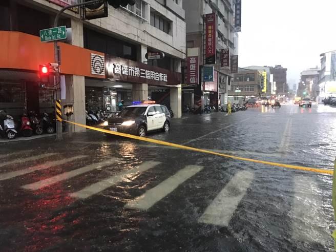 高雄傍晚雷電交加,驟降豪雨,市區新興區路段出現淹水現象,警方拉起封鎖線警戒。(讀者提供/石秀華高雄傳真)