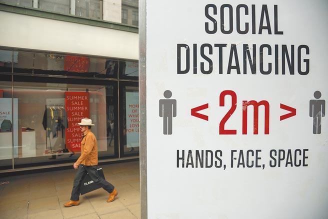 英國單日新增新冠確診病例連續兩天突破5萬人,完整注射2劑AZ疫苗的衛生大臣賈維德17日也證實受感染,出現輕微症狀。圖為在英國倫敦,一名男子從提示人們保持社交距離的牌子旁走過。(新華社)