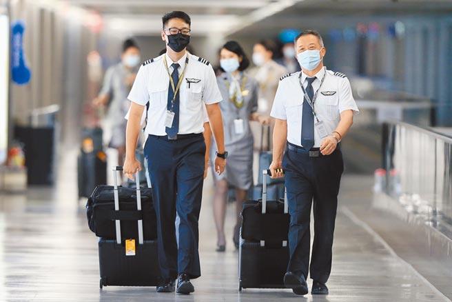 Delta變異病毒來勢洶洶,自7月21起將加強國籍航空機組員返台檢疫措施。圖為桃園機場內機組員準備入境。(陳麒全攝)