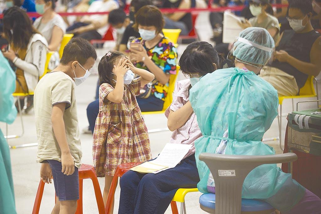 台北市開放國小教職員工等1.8萬人接種新冠肺炎疫苗,20日有接種民眾帶著孩子,小女孩看到針筒害怕到摀起雙眼,小男孩則好奇看著施打過程。(杜宜諳攝)