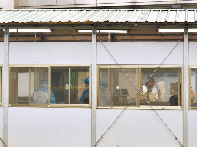 桃園市20日新增案15543為20多歲男性教練,9天住了5家旅館,據了解同行者不只1人,桃園市衛生局緊急調查中。圖為衛福部桃園醫院採檢作業。(賴佑維攝)