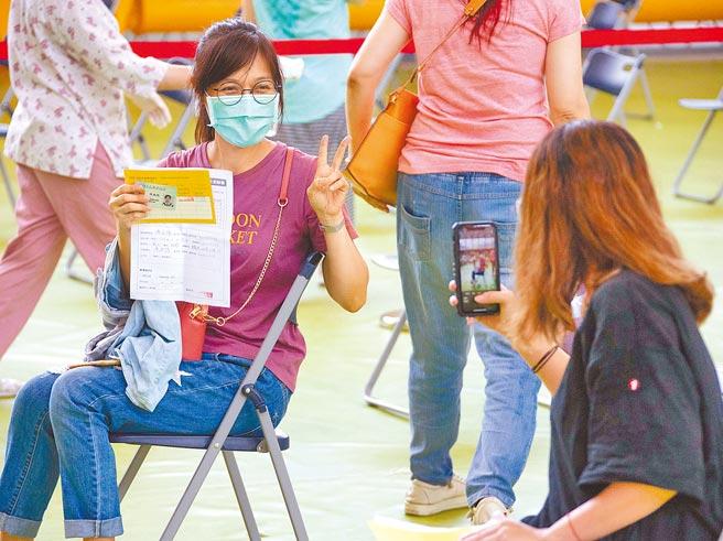 因應暑假後要開學,新北公私立國小教職員已陸續分流接種,聯合醫院21日在大觀國中設立接種站。一名教職員施打疫苗前,不忘請同事幫忙拍照,紀念難得的一刻。(羅永銘攝)