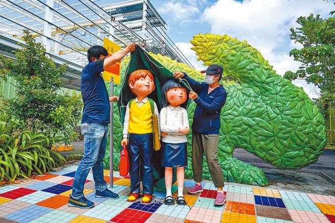 宜蘭縣政府為了防颱,21日將幾米的繪本作品「等車的男孩與女孩」等裝置藝術,以帆布覆蓋保護。(李忠一攝)