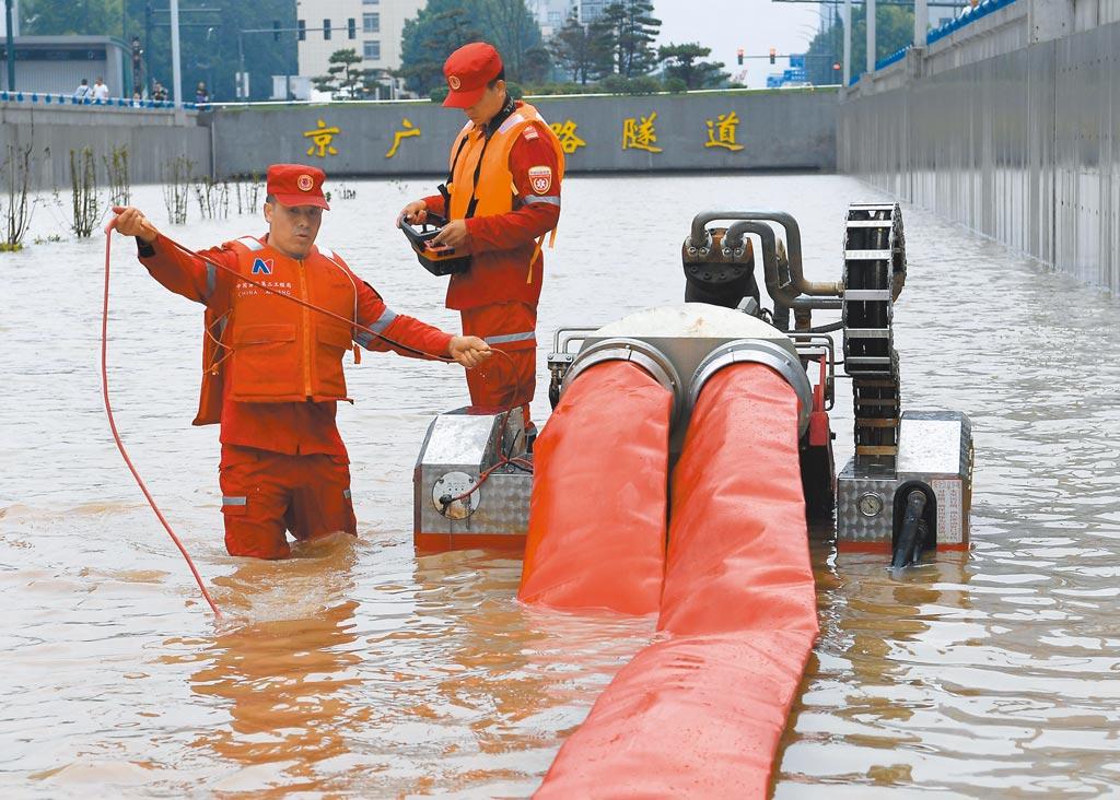 大陸河南鄭州連日遭遇暴雨,鄭州市區內的京廣路隧道,20日5分鐘內就被淹平,救援人員22日在隧道口進行排澇作業。(新華社)