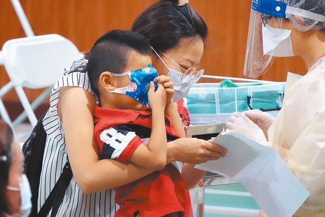 全台已累積589萬人接種疫苗,圖為新北市三重區二重國小施打站,1位陪同家長前來的小男童,用口罩遮住眼睛,不敢直視打針畫面。(黃世麒攝)