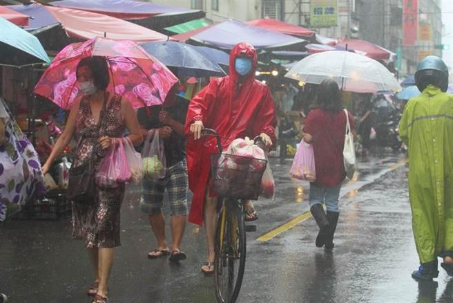 中央氣象局24日解除中颱烟花海上颱風警報,但受到外圍環流影響,北市出現間歇性大雨,讓出門買菜的民眾淋了一身濕。(張鎧乙攝)