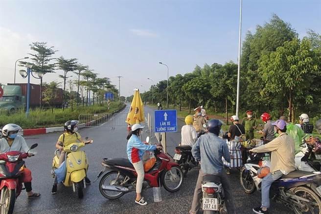 越南疫情嚴峻,政府23日晚上宣布,首都河內周六(24日)起「封城」15天。圖為一些越南民眾24日騎機車想要進入河內,遭到軍警設路障阻擋。(圖/美聯社)