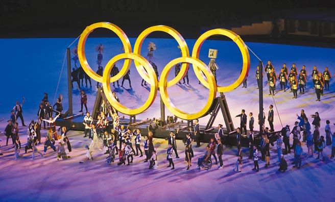 東京奧運開幕式「永恆傳承」表演,由木匠拉出木造五環,木頭來源是1964年首次東京奧運各國代表團種下的樹,展現從1964年傳承到2021年的意象。(季志翔攝)