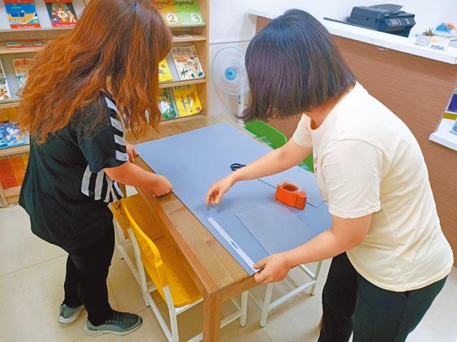 補習班有條件開放,業者假日不休息備課,並趕工製作學生用餐隔板。(張毓翎攝)
