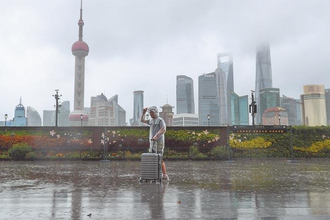 72年來7月最強的烟花颱風侵襲大陸,上海外灘江堤區域已拉起警戒線,臨時關閉。圖為一名遊客在外灘冒雨行走。(中新社)