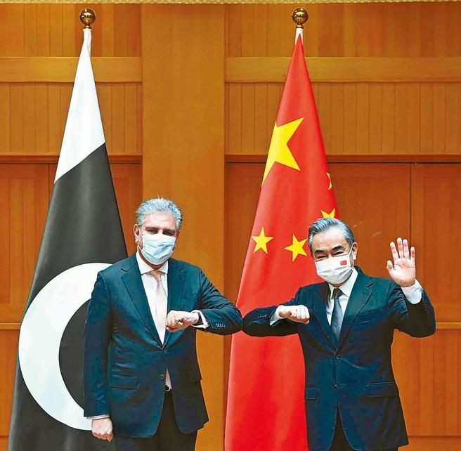 大陸外交部長王毅(右)24日與巴基斯坦外長庫雷希舉行對話,雙方將推動阿富汗各鄰國開展協調合作,探討構建鄰國涉阿合作平台。(新華社)