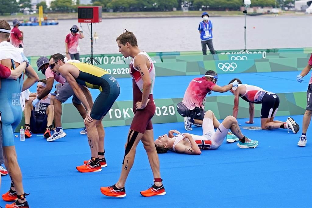 東京夏季氣候炎熱、潮濕,26日不少男子鐵人三項東奧選手在完賽後,體力透支倒地。(圖/美聯社)
