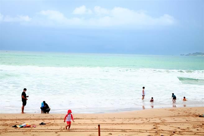 警戒降級首日南灣插紅旗,但一早仍陸續出現遊客,尤以親子客居多,大手拉小手戲水玩得不亦樂乎。(謝佳潾攝)