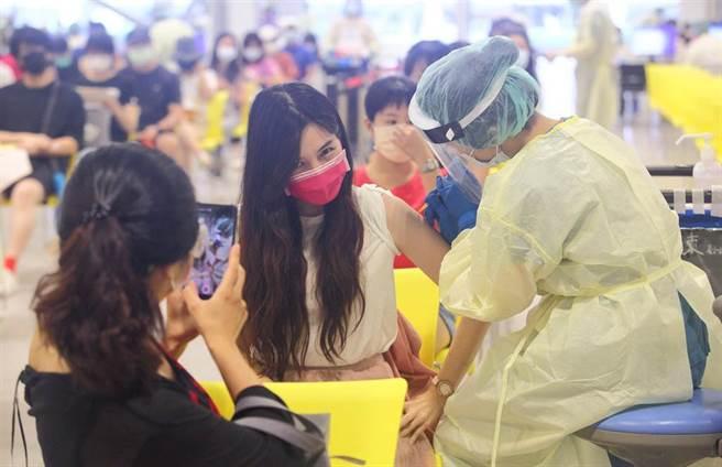 國高中教師專案人員27日在北市花博接種站施打疫苗時,互相用手機拍照留念。(圖/記者張鎧乙攝影)