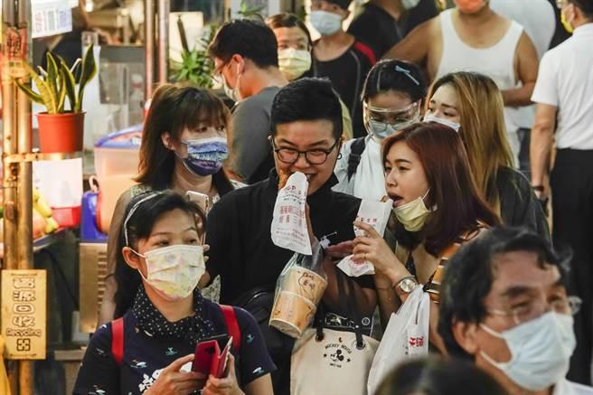 廟口夜市27日傍晚開始湧現大量人潮,有的遊客還脫下口罩邊走邊吃。(黃子明攝)