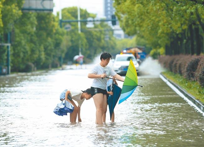 烟花颱風過境,浙江省寧波市河網水位節節攀升,造成局部道路積水,市民涉水行走。(新華社)