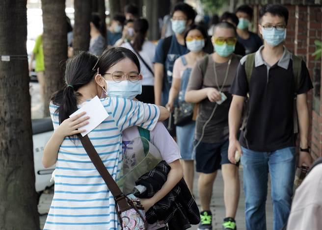 110學年度大學指考28日登場,考生依規定戴口罩,在上午8點前後陸續抵達考場並量體溫,無法入內陪考的家長在門口給考生擁抱鼓勵。(姚志平攝)