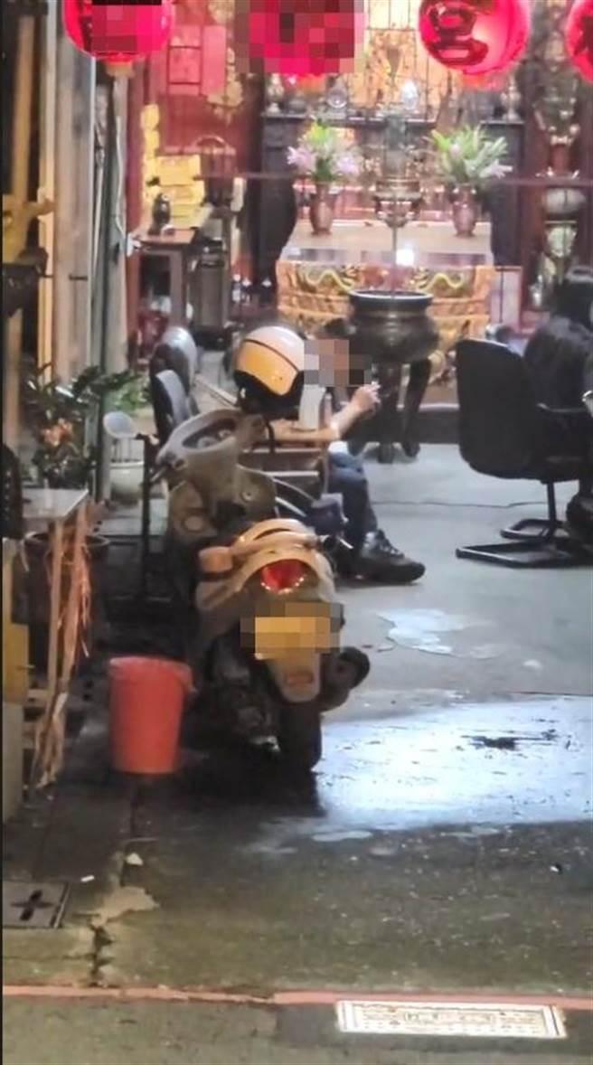 嚴姓警員在神壇前脫口罩抽菸、怠勤逾半小時,分局調查後開單告發並記過處分。(讀者提供/石秀華高雄傳真)