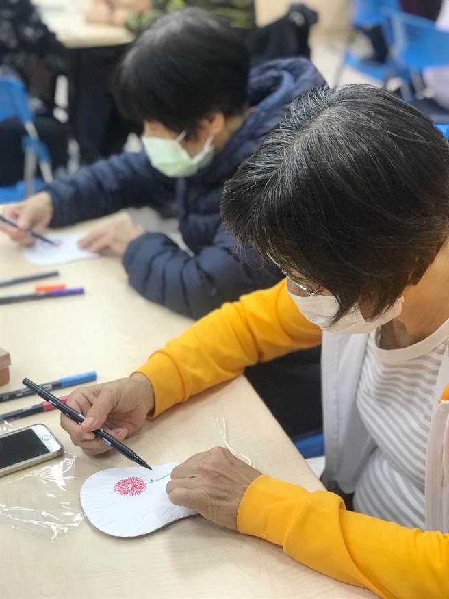 學員專注的彩繪心靈團扇。(攝影/張淑玲)