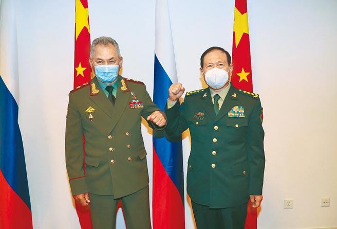 拜登點名中、俄對美威脅日增,中國國防部長魏鳳和(右)與俄羅斯國防部長紹伊古(左)28日正巧在塔吉克首都杜尚貝,參加上海合作組織成員國防長會議,兩人進行會晤時,互碰手肘致意。(新華社)