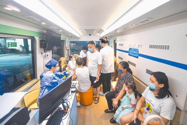 大陸科學團隊領先全球發表「霧化吸入式新冠疫苗」臨床試驗結果,只要1/5肌肉注射量便可生效。圖為28日浙江杭州首輛新冠疫苗移動接種車,在杭州火車東站為旅客免費接種。未注射或僅注射過一劑滅活疫苗的旅客,憑車票都可前來接種。(中新社)
