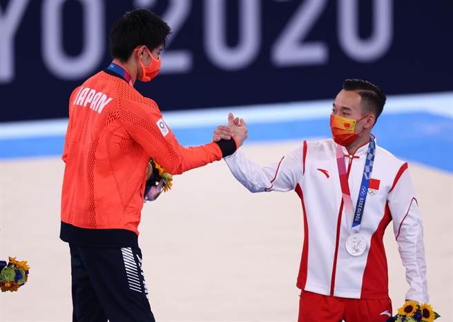 橋本(左)以0.4分的差距擊敗肖若騰,引發陸酸民攻擊。圖為兩人領獎後彼此握手致意。(圖/路透社)