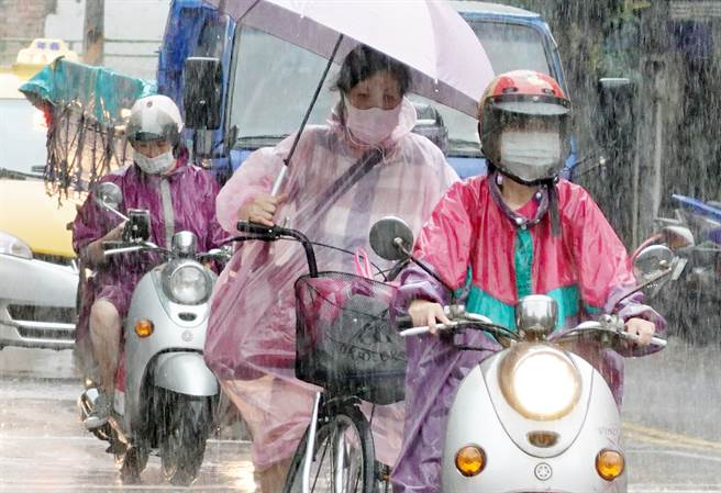 大台北地區31日下午一場大雨苦了騎士,穿著雨衣或撐傘繼續前行。(姚志平攝)