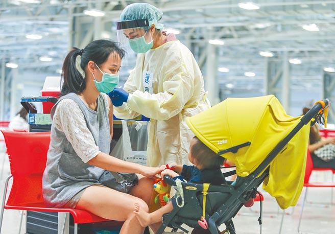公費疫苗預約平台日前開始運作,位於圓山爭豔館的接種站,一位母親帶著幼兒前來,一邊接受護理師接種。(粘耿豪攝)