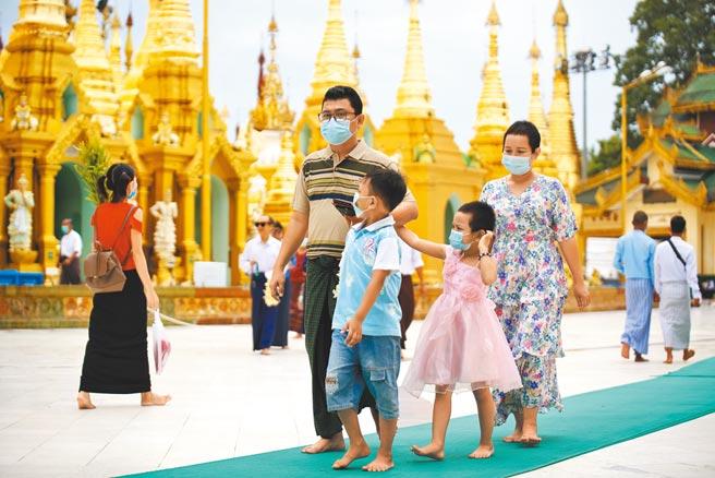 緬甸2月軍事政變後局勢動盪,加上醫療能量吃緊,導致疫情急速飆升。英國更在聯合國安理會警告,未來兩周緬甸5400萬人口中恐怕有一半染疫。圖為緬甸民眾戴口罩,參觀世界佛教聖地仰光大金塔。(新華社)
