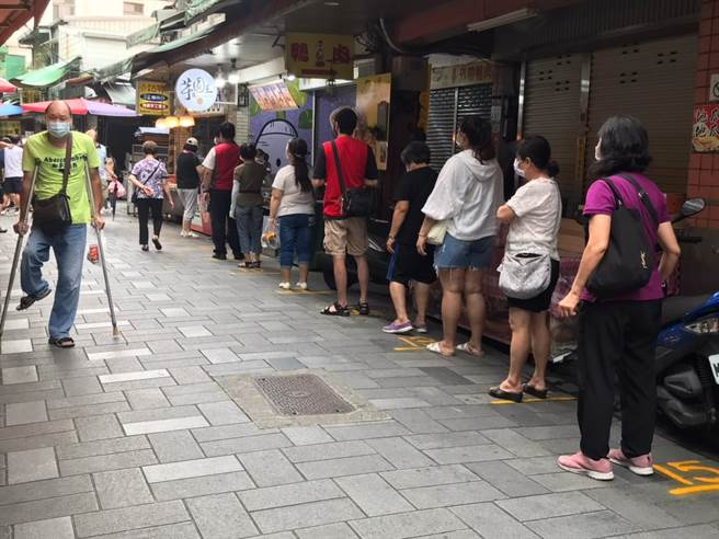 新北市金山老街今(1日)上午稍微出現人潮,約有10餘名民眾在場排隊購買金山知名的鴨肉,區公所會同警方持續到場宣導防疫措施。(金山區公所提供)