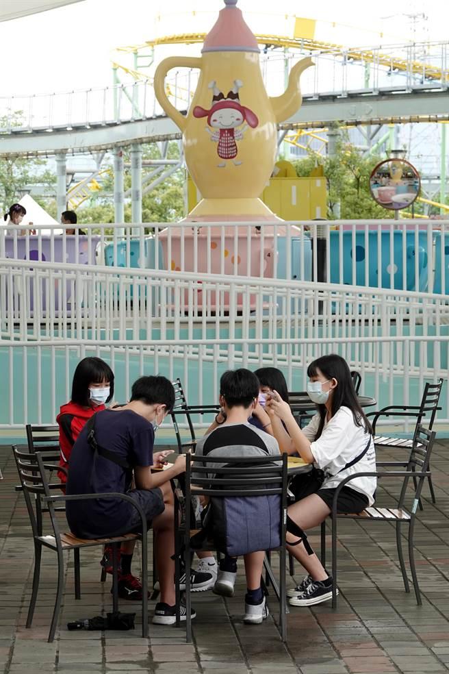 因執行嚴格的防疫措施,讓等待的時間拉長,一群青少年趁著空檔,圍在一起玩手機遊戲打發時間。(黃世麒攝)