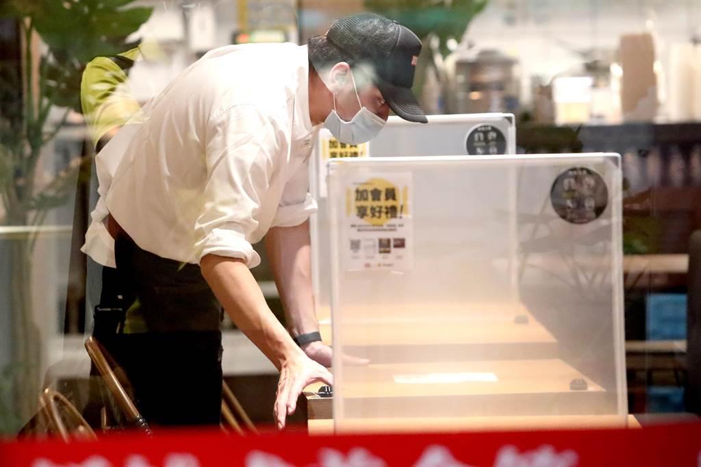 雙北將宣布開放餐飲內用,北市一家餐廳的店員為內用區架設隔板,準備迎接顧客上門。(鄭任南攝)