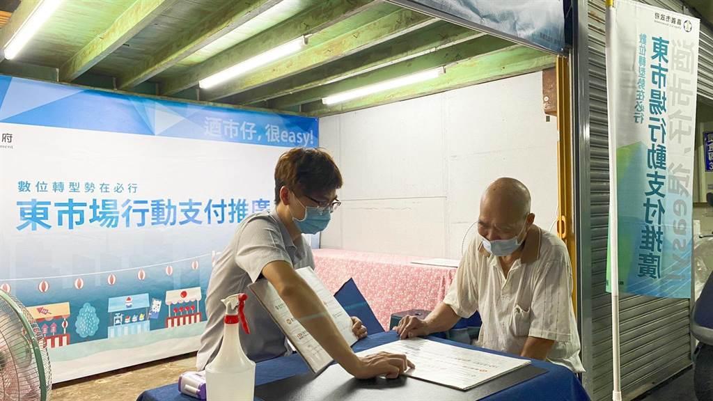 嘉義市政府在東市場內設立推廣站,輔導攤商及消費者使用行動支付。(嘉義市政府提供)